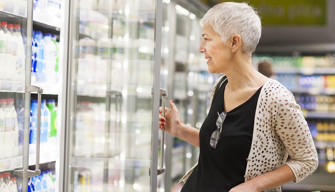 Mature woman shopping at supermarket opening fridge