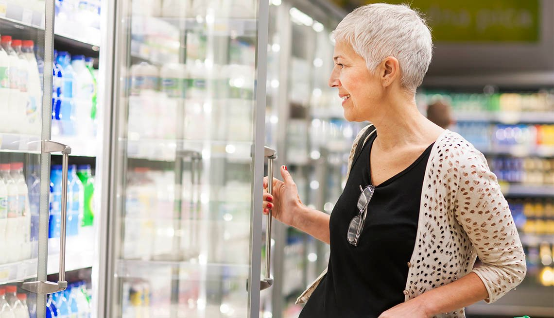 Mature woman shopping at supermarket opening fridge