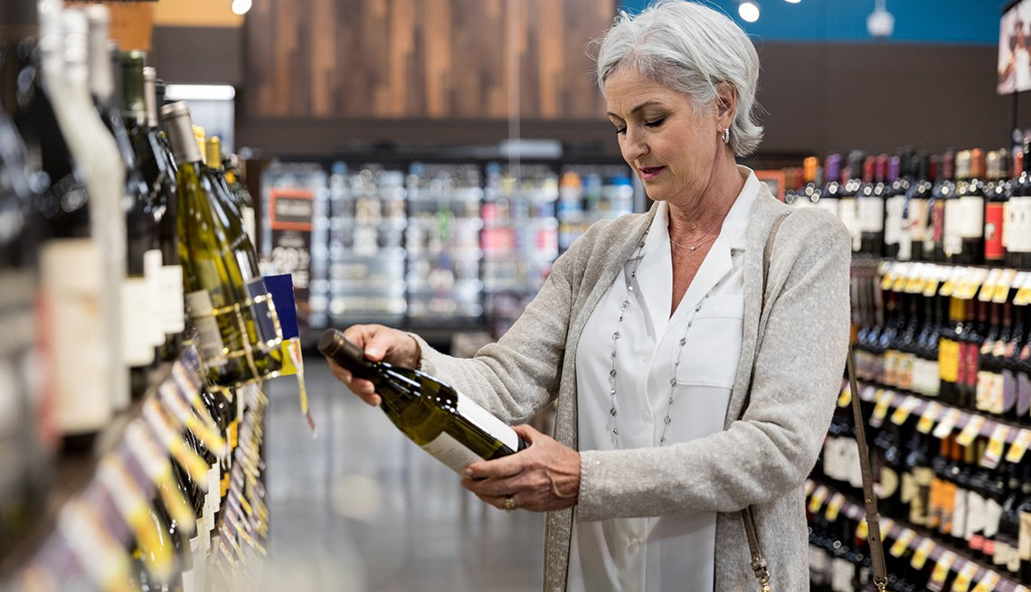 Standing in the liquor aisle of the grocery store, the mature adult woman reads the label on a bottle of wine.