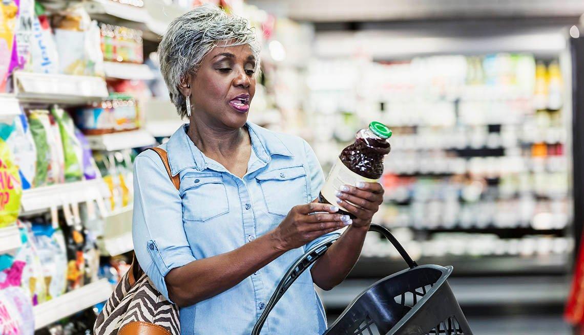 Una mujer lee la etiqueta nutricional de un frasco