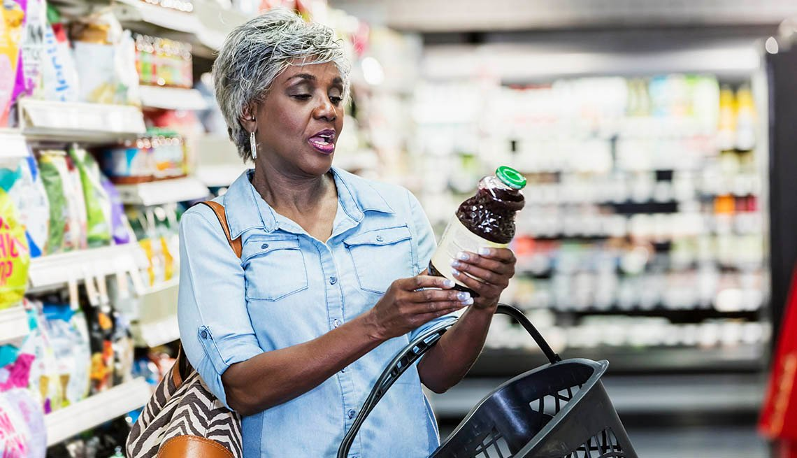 A senior African-American woman in her 60s shopping in a grocery store, carrying a shopping basket. She is reading the nutrition label on a bottle.