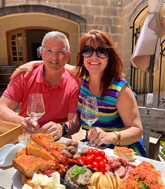 peter and eileen azzopardi enjoy an italian feast and wine on an outdoor patio