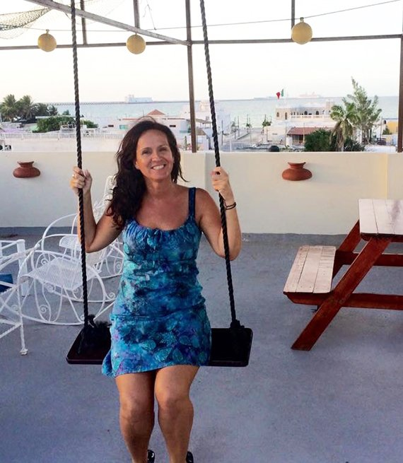 sonya vangelderen sits on a swing on a patio with a view of the ocean