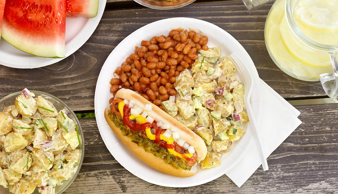 BBQ Hotdog with Mustard, Relish, Ketchup and Onions with Potato Salad and Baked Beans at a Picnic