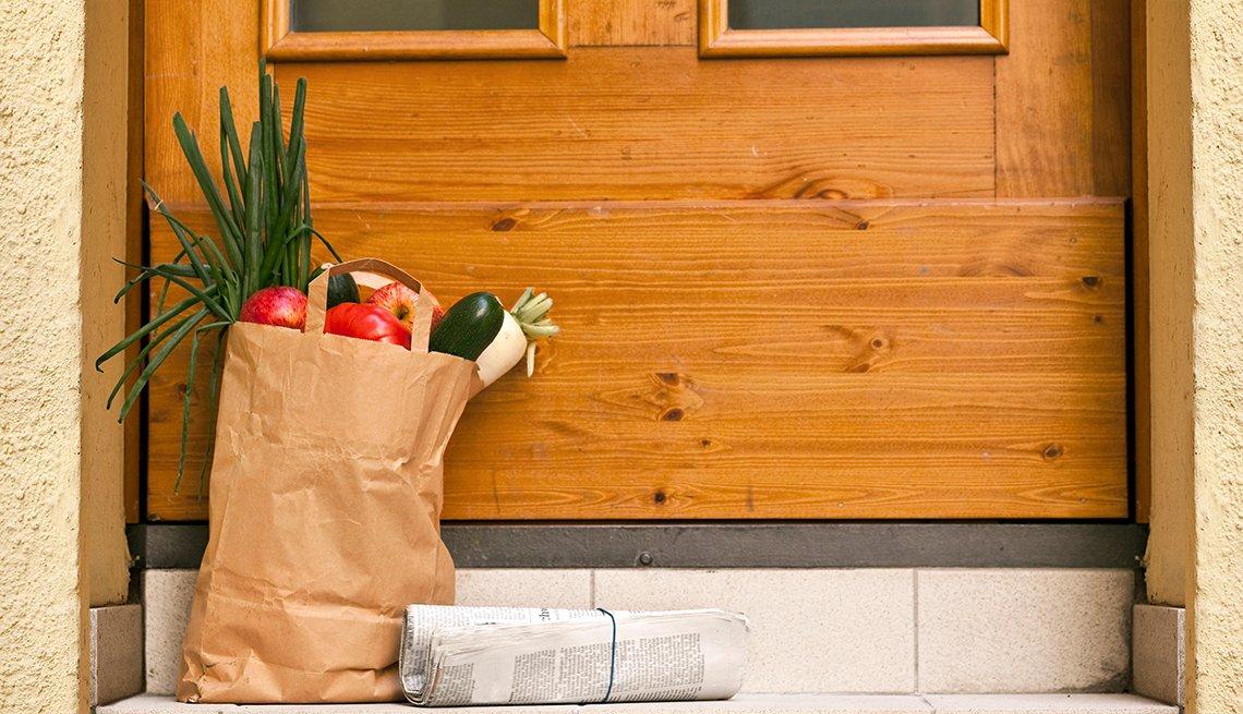 Bolso de víveres y un periódico frente a la puerta de una residencia