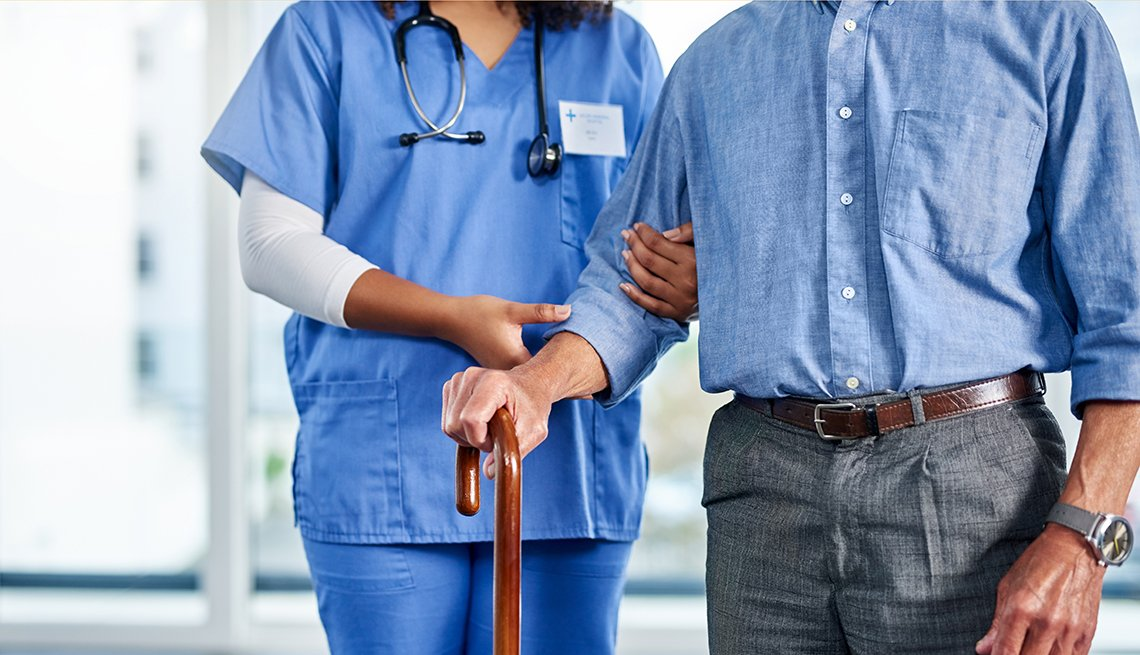 a nurse or physical therapy assistant is helping support an older man walk with a cane