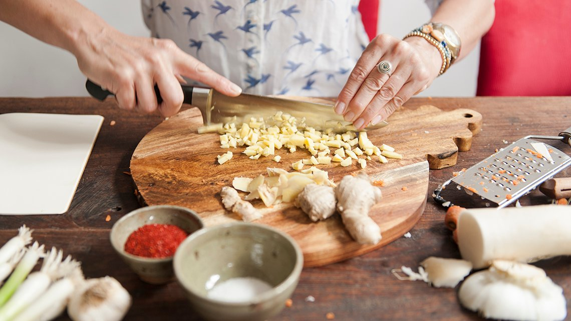 woman chopping ginger on a cutting board with garlic and other ingredients around it