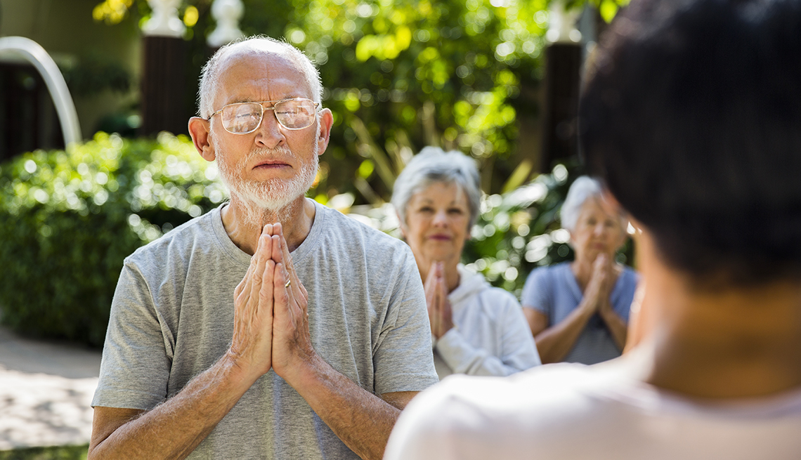 a group of older people meditating outdoors on a sunny day