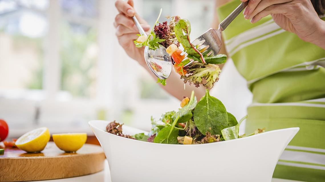 Una mujer revuelve una ensalada