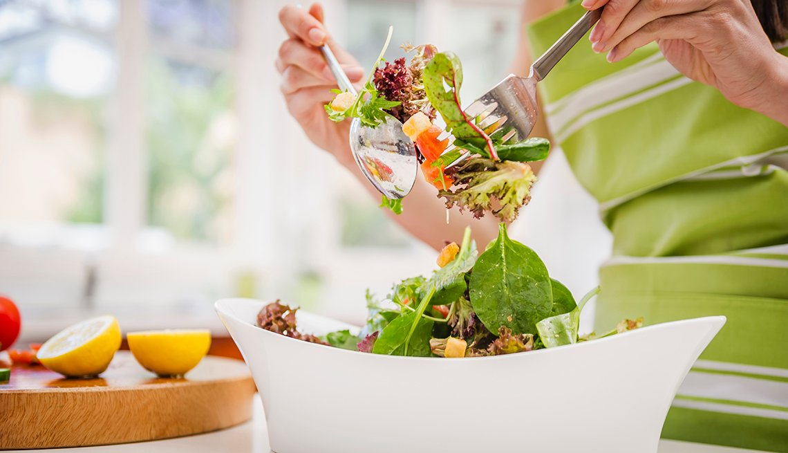 a woman tosses a fresh healthy looking salad with lemon dressing at home in her kitchen