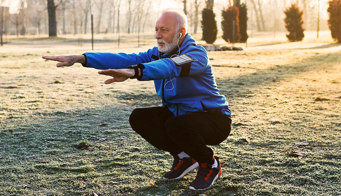 older man performing a deep squat outdoors while exercising