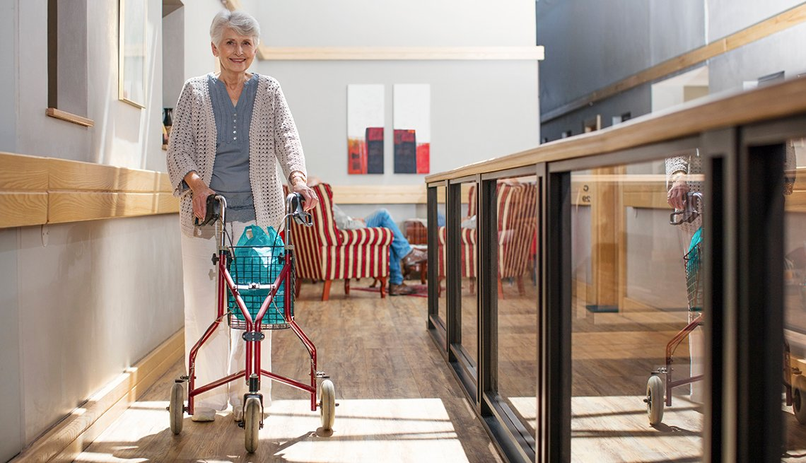 senior woman indoors using a three wheeled walker