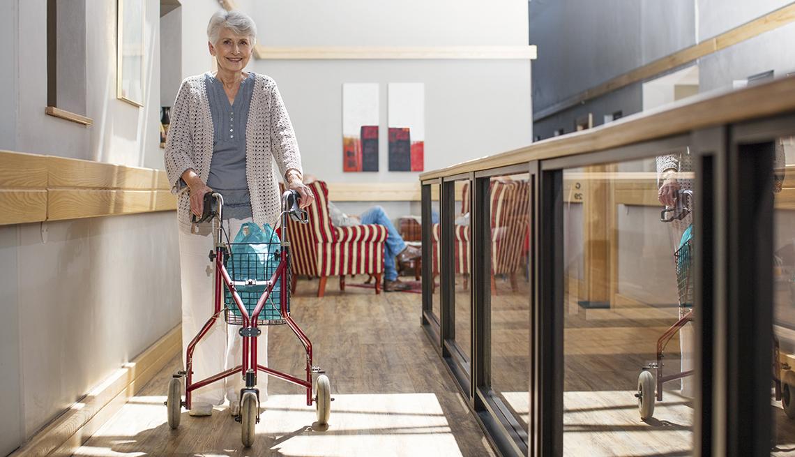 senior woman indoors using a three wheeled walker