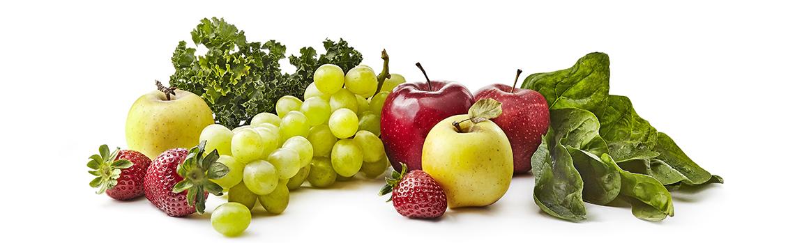 Uvas, fresas, manzanas verdes y rojas y vegetales de hoja verde