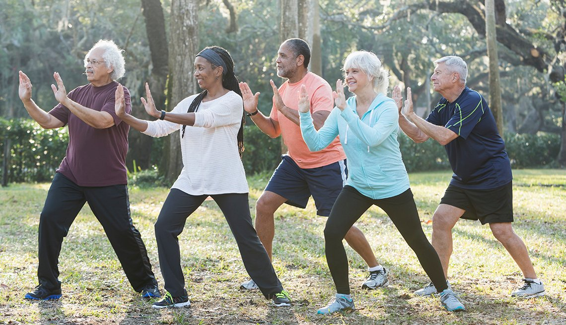 diverse group of five seniors practicing tai chi outdoors