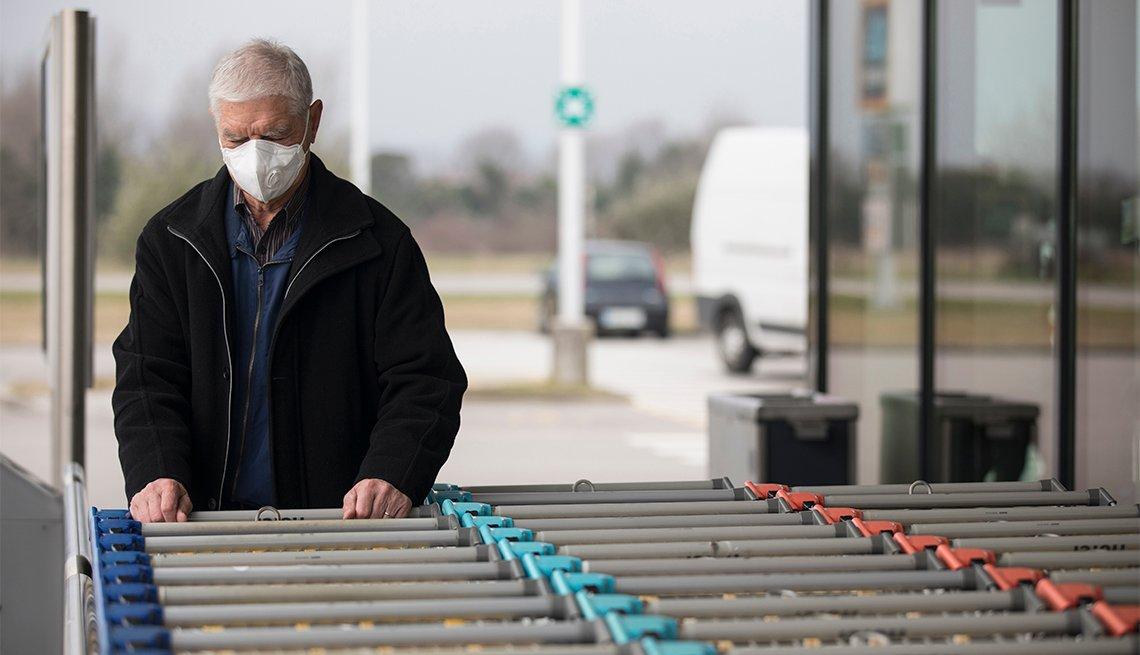 Un hombre mayor, usando mascarilla, visita un supermercado