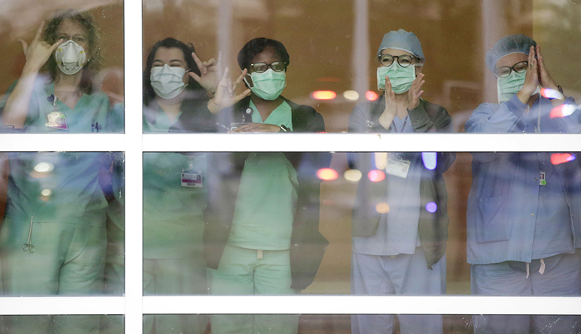 item 6 of Gallery image - Medical personnel look out a hospital window during an event called Headlights for Hope at Bailey Medical Center in Owasso, Okla., Wednesday, April 1, 2020.
