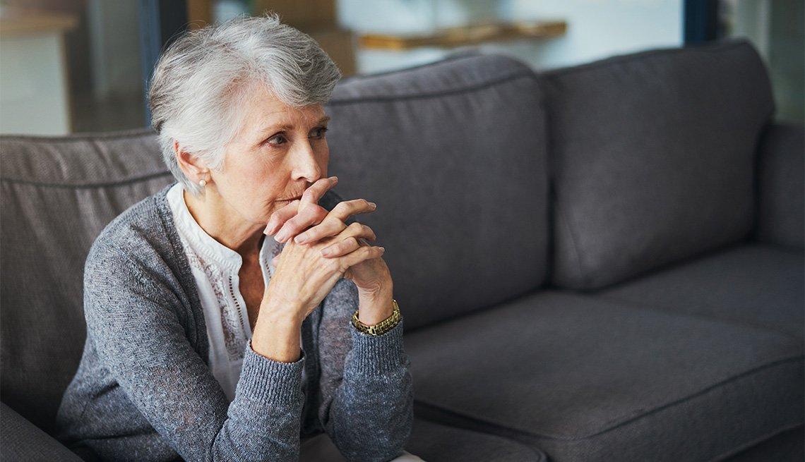 Una mujer mayor preocupada sentada en un sofá