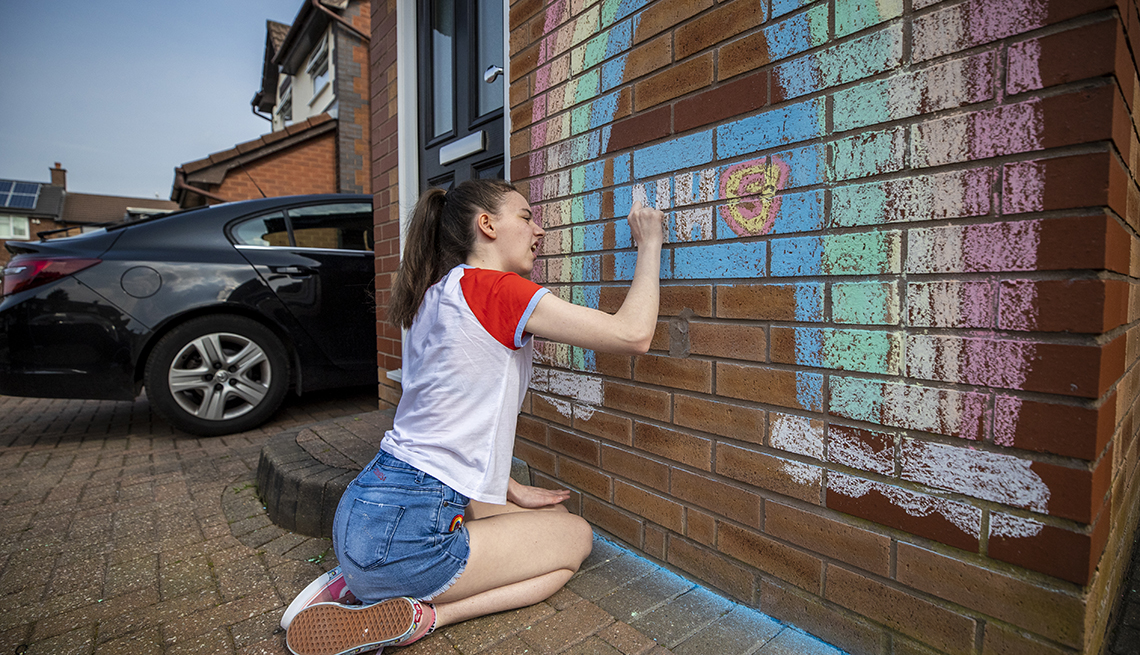 item 9 of Gallery image - A teenager draws a rainbow and an NHS logo on the wall of her house in Liverpool in support of the NHS as the UK continues in lockdown to help curb the spread of the coronavirus. (Photo by Peter Byrne/PA Images via Getty Images)