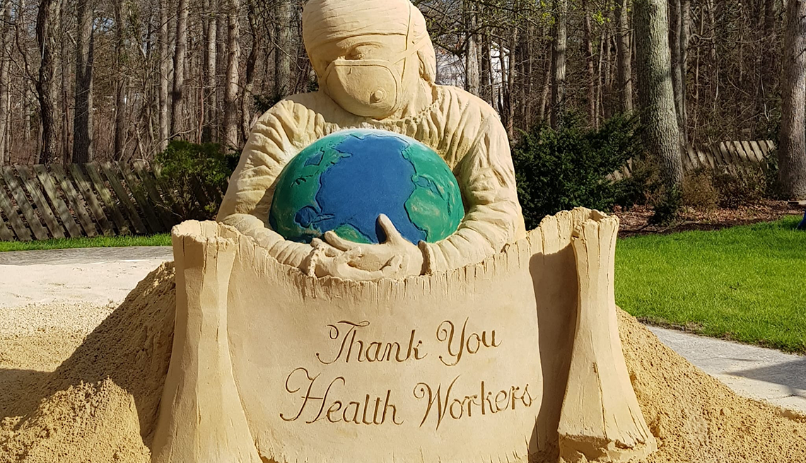item 3 of Gallery image - A masked medical worker cradles the world in a six-ton sand sculpture built by artists John Gowdy and Laura Cimador-Gowdy at their home in Galloway, New Jersey.