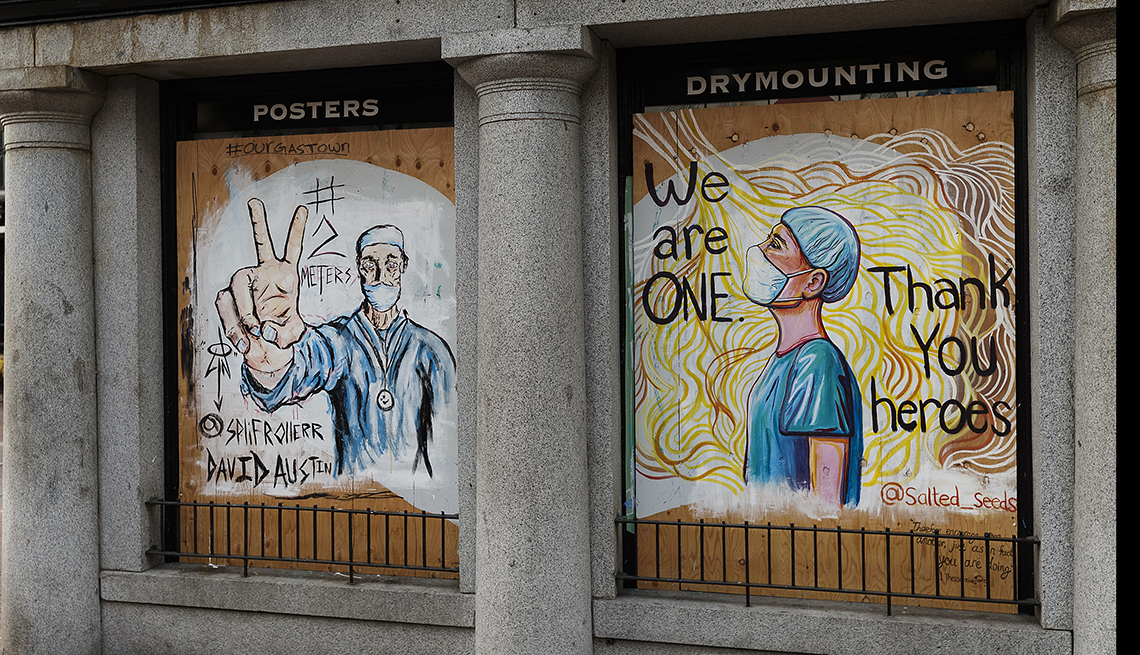 """A mural of doctors reading """"We are ONE"""" and """"Thank You heroes"""" is on display on a boarded up window in Gastown on April 09, 2020 in Vancouver, Canada. Gastown, normally a popular tourist area in Vancouver is quiet as all non-essential retail has been clos"""