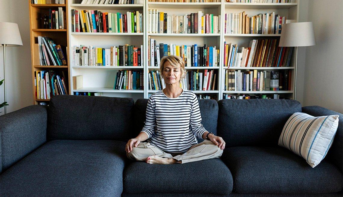 Una mujer medita en la sala de su hogar