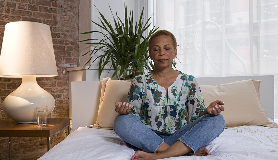 Una mujer practica la meditación sentada en su cama