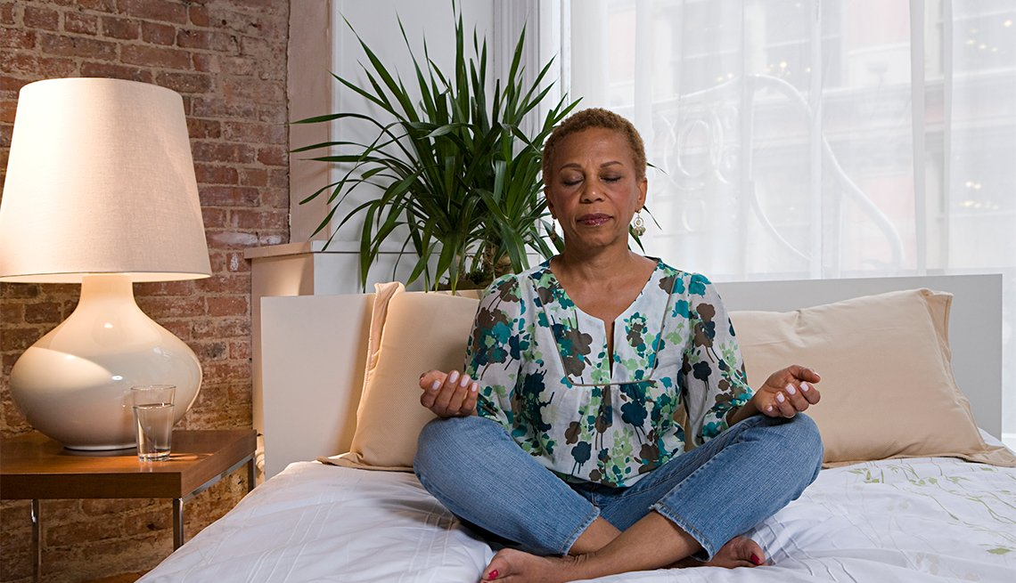 African American woman sits cross-legged on a bed and meditates