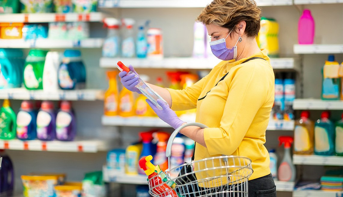 Mid adult woman with protective face mask and protective gloves in supermarket, holding disinfection product and reading label during covid-19 outbreak