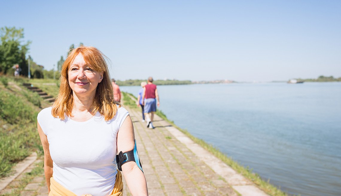 Mature  woman having walking on a trail by water
