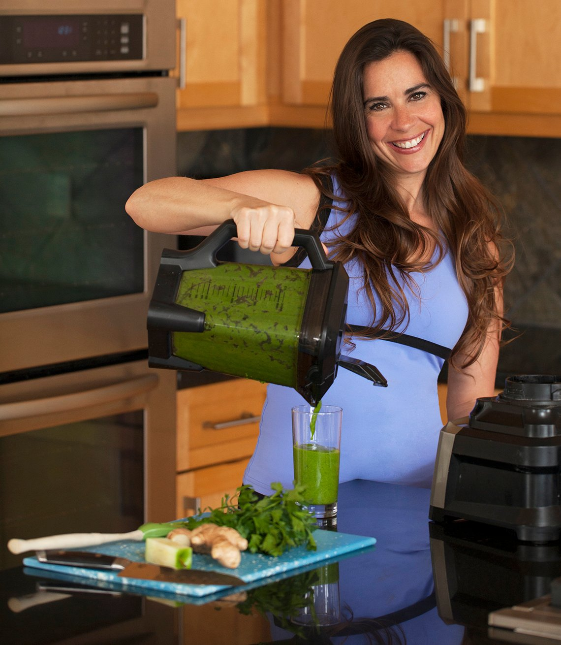 devin alexander in the kitchen pouring a blender full of happy tummy greens juice
