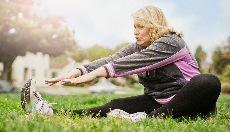Una mujer hace estiramiento en un parque