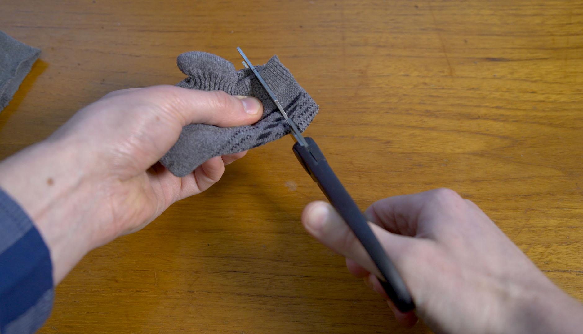 Manos usan una tijera para hacer un corte en una media