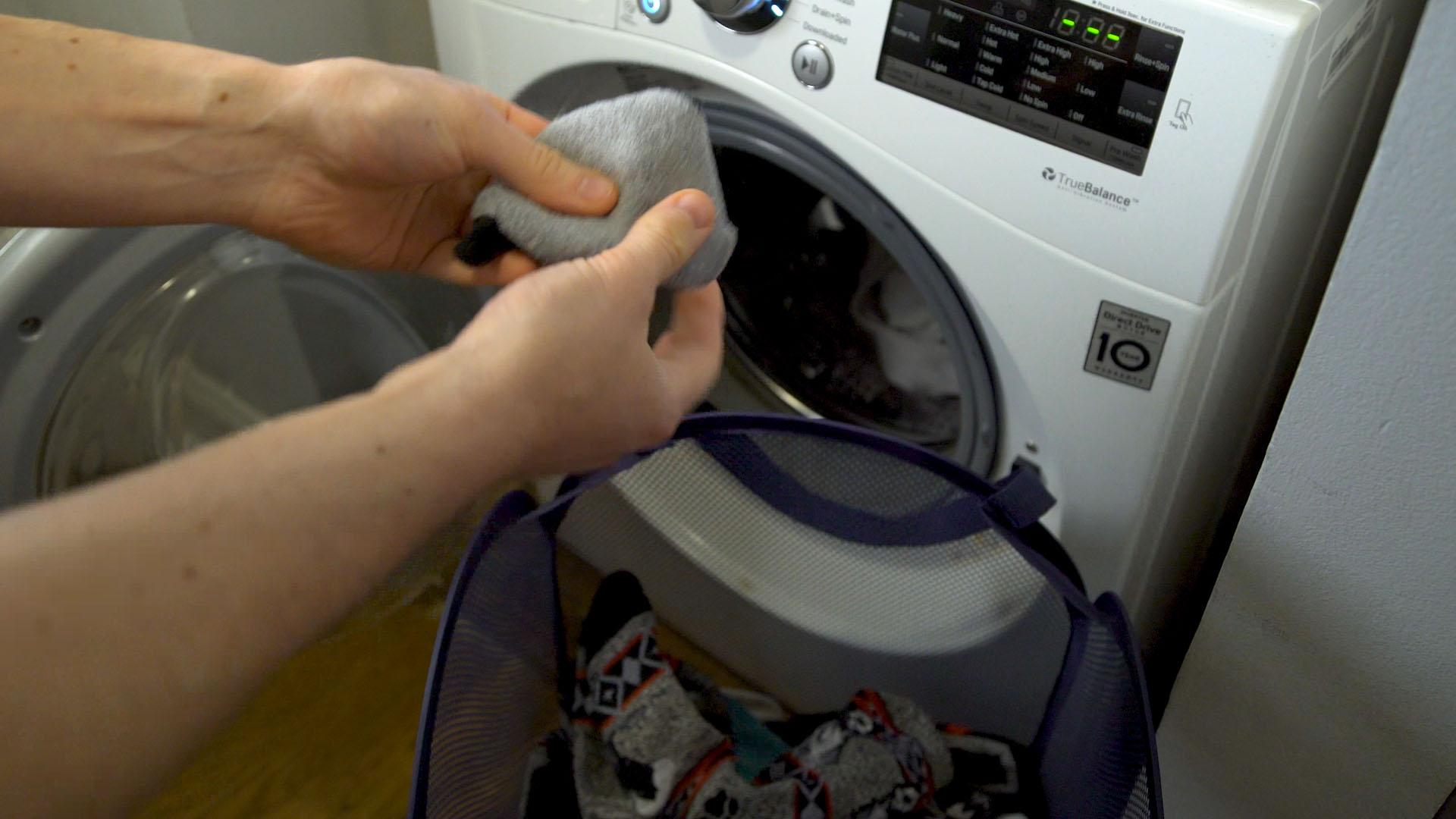Manos de una persona coloca ropa sucia en una lavadora