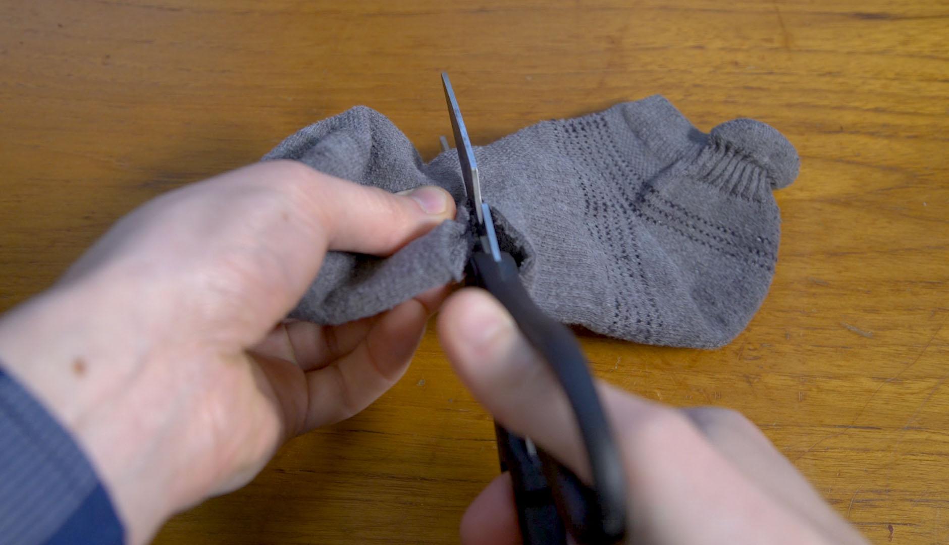 Manos usan la tijera para cortar una media