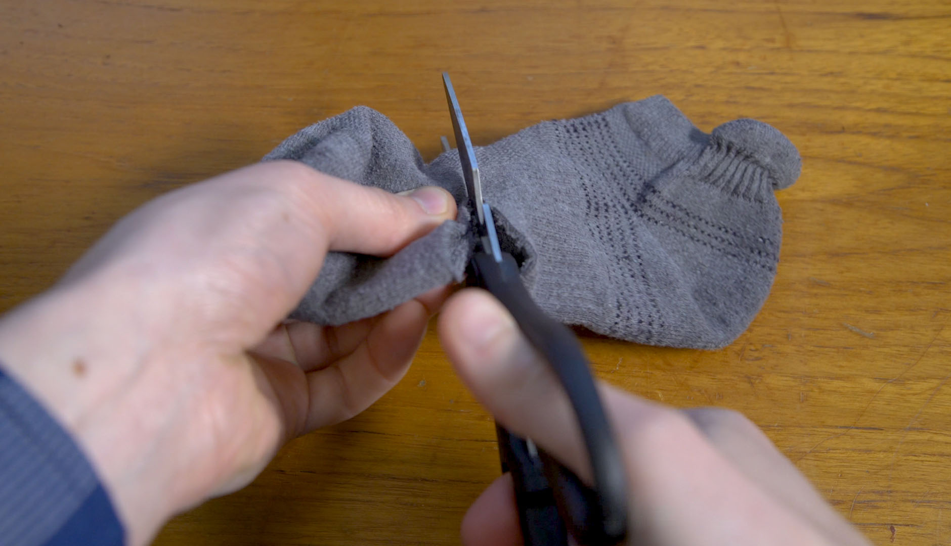 hands cutting off end of the sock