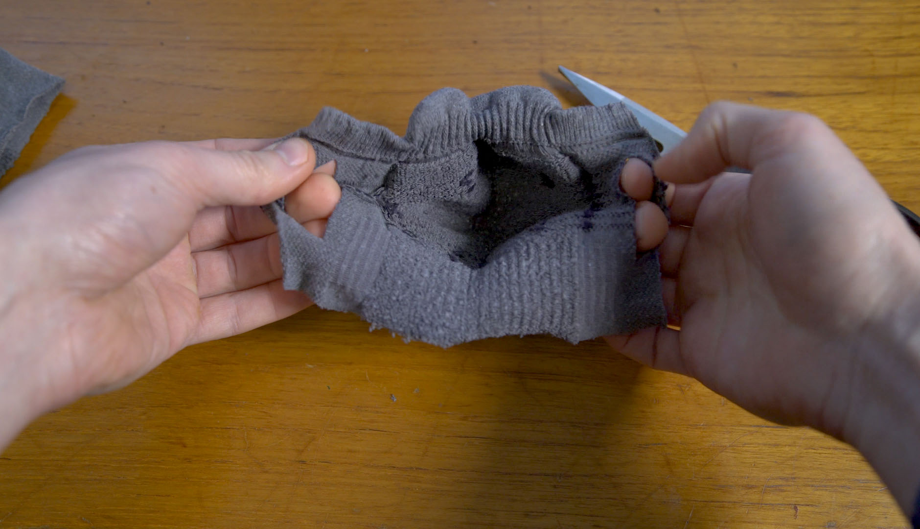 hands holding sock face mask with loops