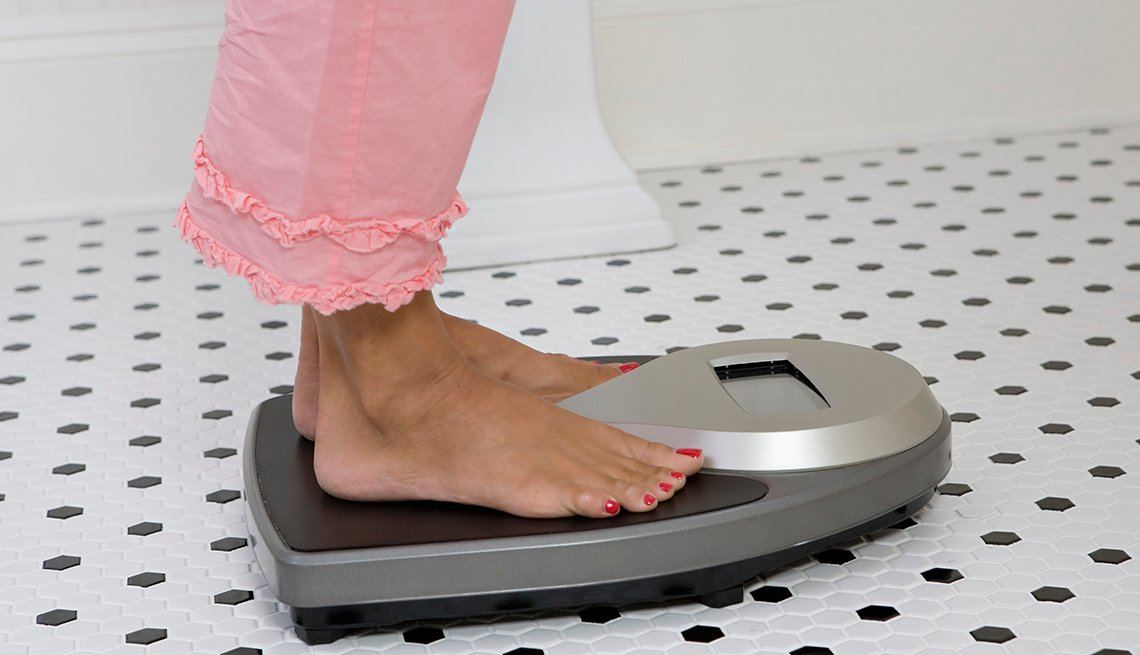 view of a womans feet on a scale weighing herself