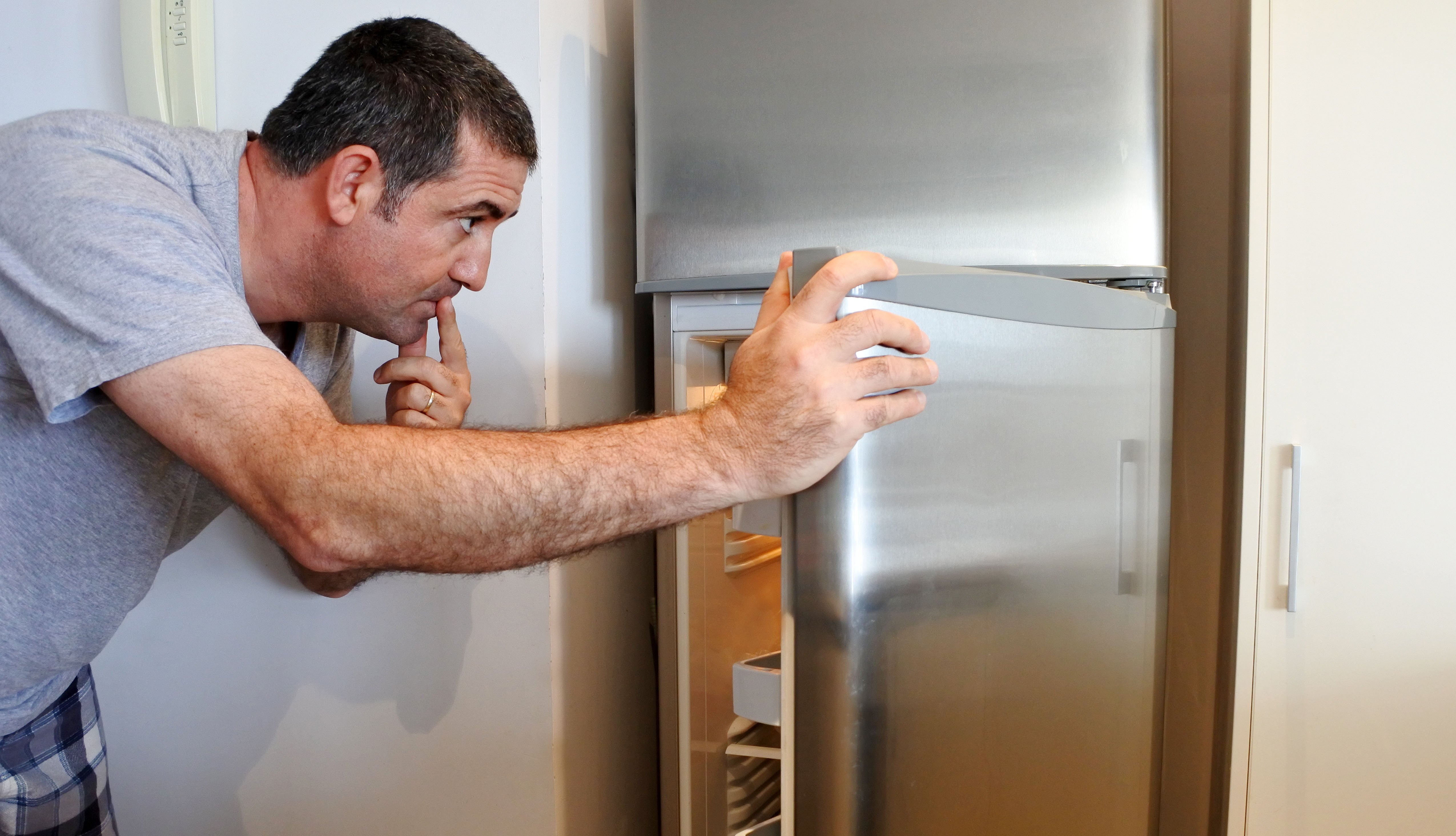 man wearing pjs looks in the fridge for something to eat