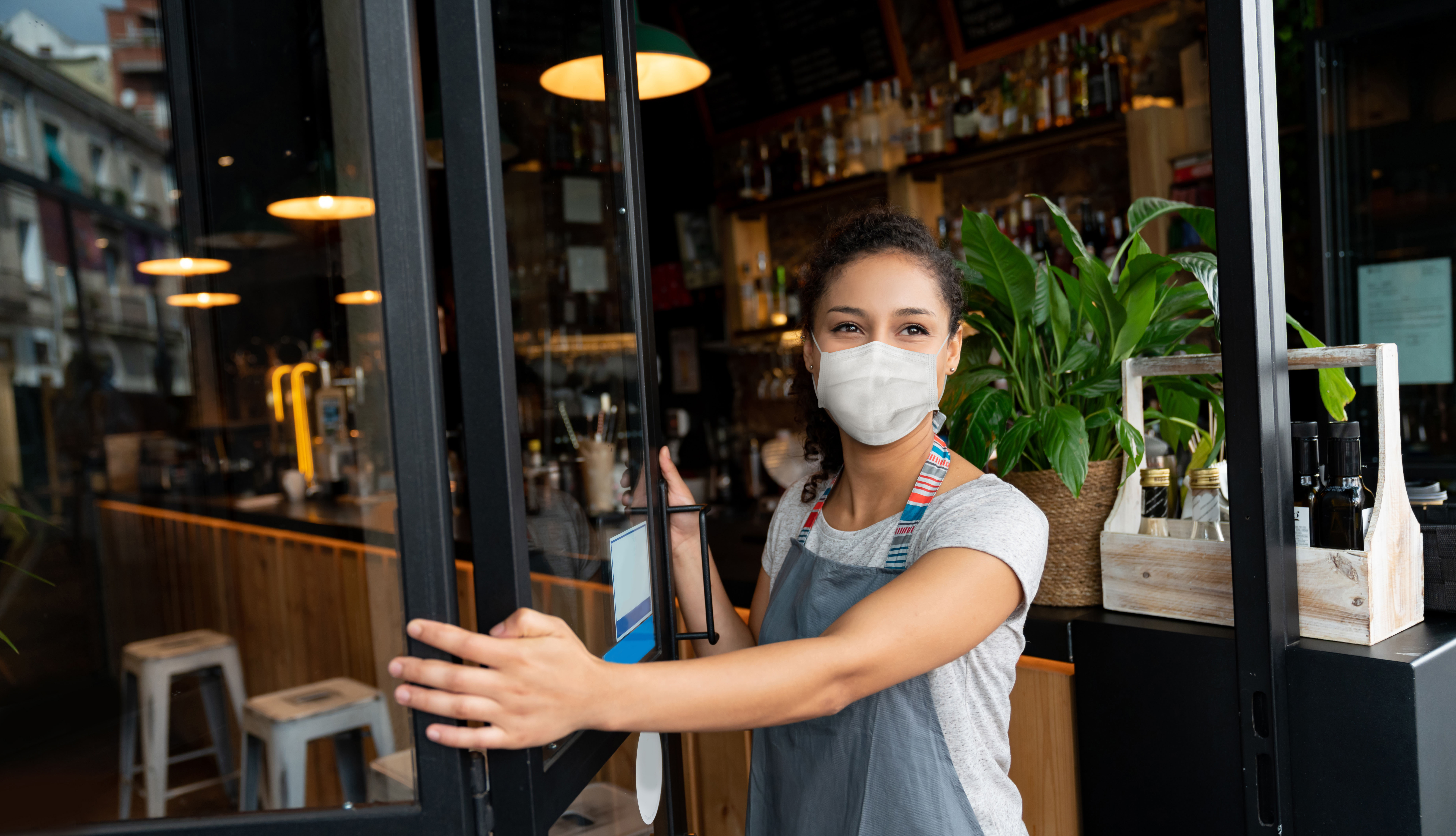 business owner opening the door of her restaurant while wearing face mask