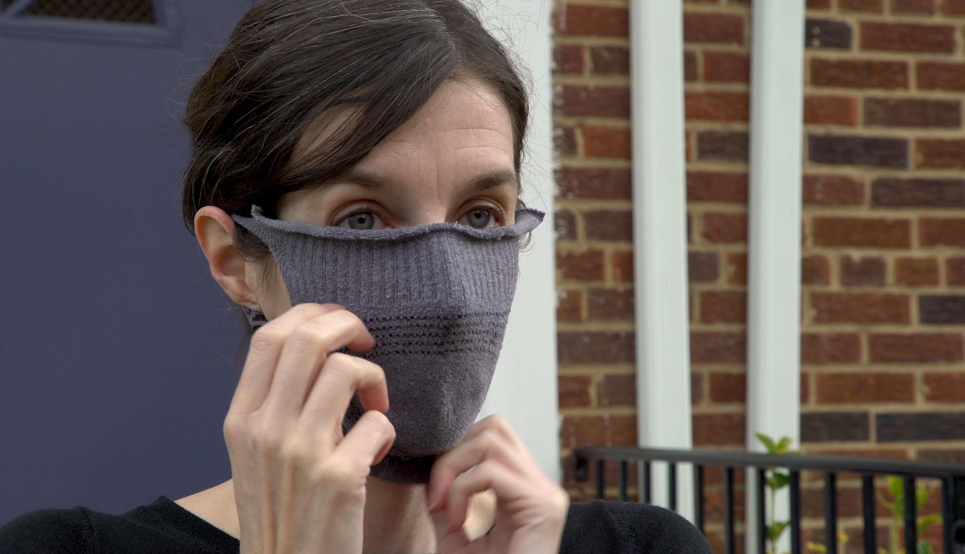 Una mujer se ajusta una mascarilla hecha con una media