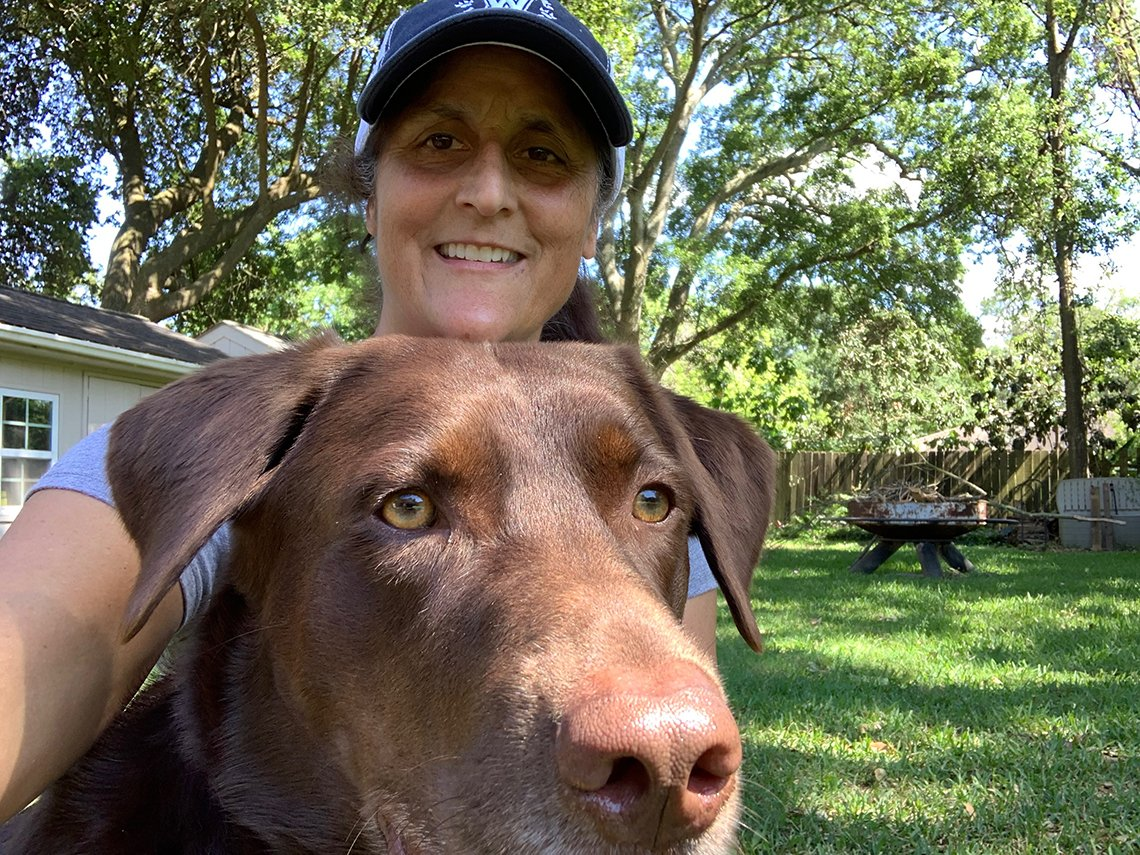 a woman in a baseball cap poses with her chocolate labrador retreiver dog in her home back yard