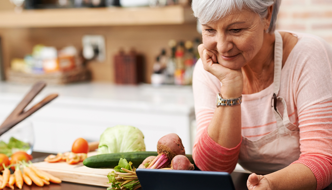 woman in kitchen looks at tablet, vegetables on counter to her right
