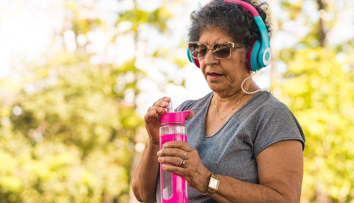 Una mujer toma agua mientras se ejercita al aire libre
