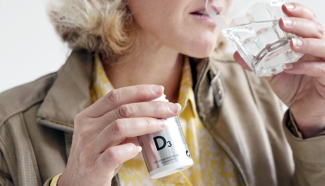 Una mujer sostiene un frasco de vitamina D en una mano mientras toma agua