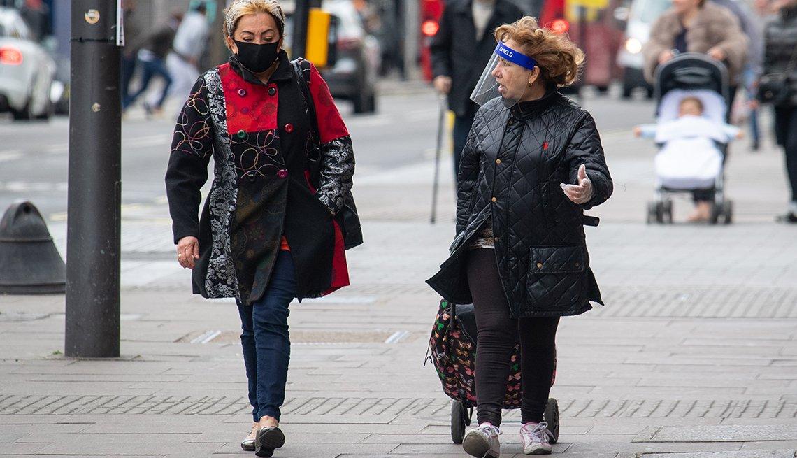 Dos mujeres caminan por una calle, una lleva mascarilla y la otra un protector facial