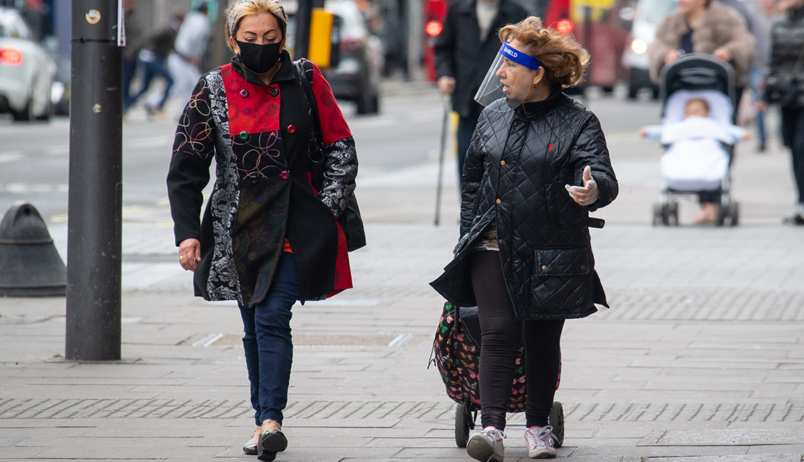 Two women wearing a protective face mask and a plastic face shield on a London street.