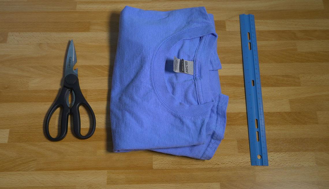 Tijeras, una camisa de algodón doblada y una regla sobre una mesa