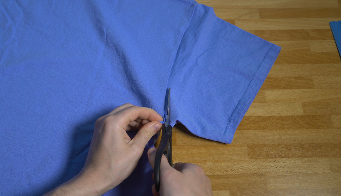 Cutting a sleeve off a cotton t-shirt with scissors.