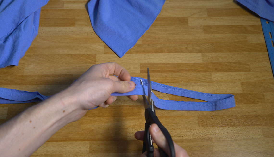 Scissors cutting through strip of a cotton t-shirt.